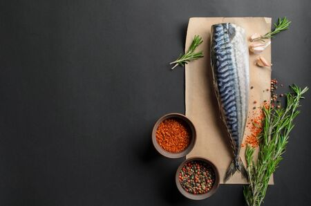 Cooking background, fresh raw mackerel on black background, top view