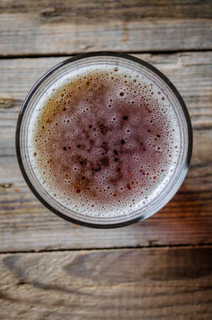 top down: glass of beer shot top down on wooden rustic table Stock Photo