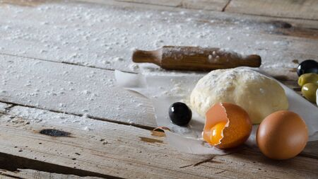 supple: elastic dough sprinkled with flour on parchment paper, one whole egg and one broken egg, and olives, and a rolling pin on a wooden board,