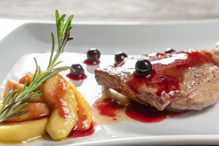 baked meat: Duck leg with caramelized apples, garlic and rosemary. In a white plate. Close-up. Stock Photo