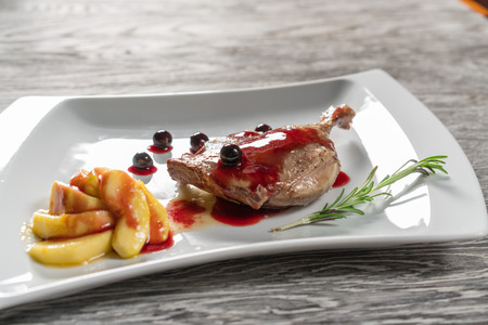 baked meat: Duck leg with caramelized apples, garlic and rosemary. In a white plate. Stock Photo