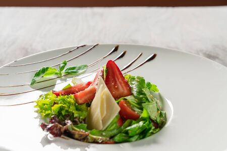 Salad greens, cheese and strawberries with balsamic sauce. Close-up. Stock fotó
