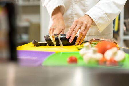 Steel worktop in the kitchen by professional. On the table, a cutting board and vegetables. The cook prepares a presentation of dishes.