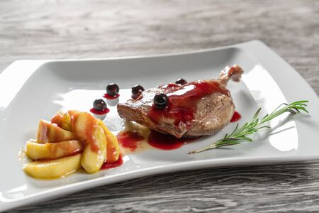 Duck leg with caramelized apples, garlic and rosemary. In a white plate. Stock fotó