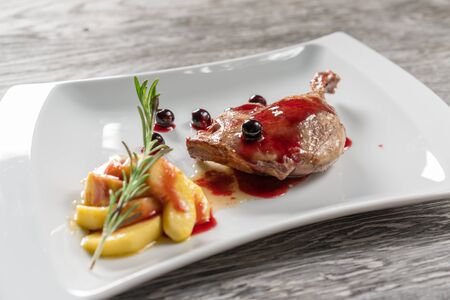 Duck leg with caramelized apples, garlic and rosemary. In a white plate. Stock Photo