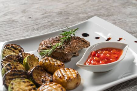 Steak with grilled vegetables and sauce on a white plate. Restaurant presentation. Side view.