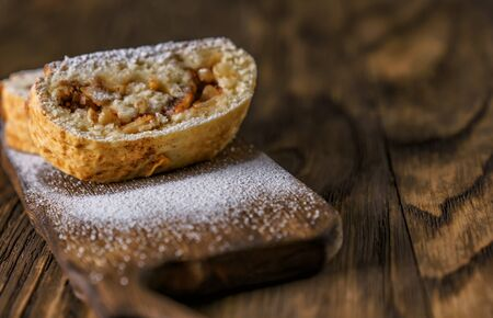 Portion dessert, strudel, with apples, nuts and cinnamon sprinkled icing sugar, laid out on an old wooden board.