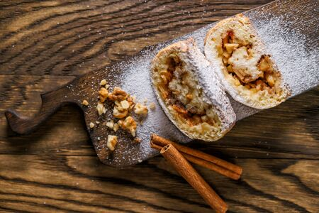 Top view of strudel with apples, nuts and cinnamon, sprinkled icing sugar, laid out on an old wooden board. Easy movement of a camera.