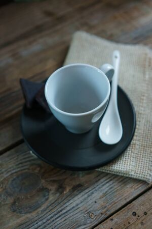 White empty cup of coffee on black saucer with a spoon on a wooden board, with pieces of chocolate