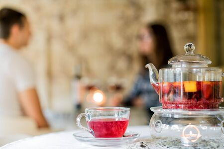 Couple of young people in the restaurant at a table with a glass of wine, blurred background, defocus. In the foreground, kettle with tea and cup.
