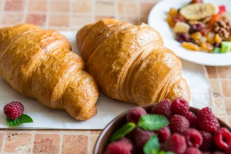 A healthy breakfast, croissants, raspberry and candied fruits.