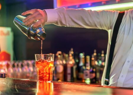 adding: The bartender makes a cocktail at the bar, pours a glass of the shaker. Stock Photo
