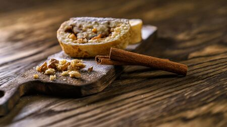 Apple strudel with nuts on a wooden board with a cinnamon stick.