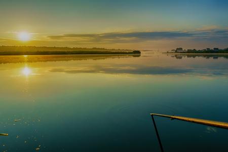Beautiful, colorful sunrise over the lake, the morning haze. Orange yellow sun.