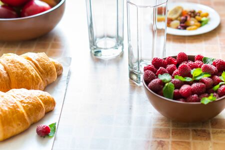Croissants and raspberries on the table, healthy and light breakfast.