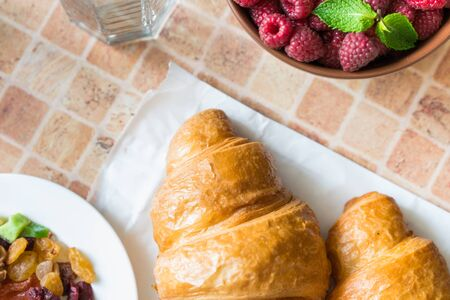 Croissants, raspberries and candied fruits on the table, healthy breakfast. View from above. Stock fotó