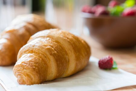 Croissants, raspberries and candied fruits on the table, healthy breakfast.