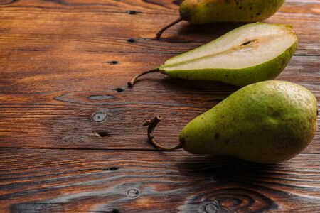 Fresh pears on the wooden background with free space for text.