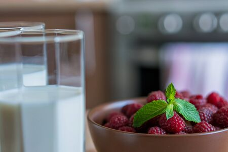 Glass of raspberry milk shake with berries on bright background