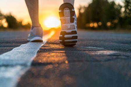 Runner feet running on road closeup
