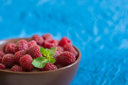 Fresh raspberry in ceramic bowl on the blue background
