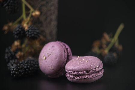 Sweet macaroons with blackberries on black bacground Stock fotó