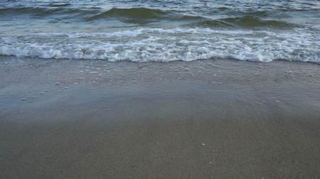 Sea waves over a sandy beach background