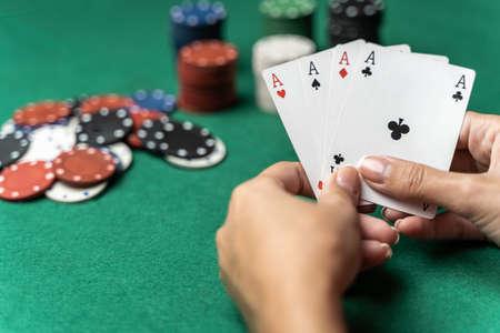 Stapel Chips und Frauenhand mit vier Assen auf dem Tisch. Pokerspielkonzept