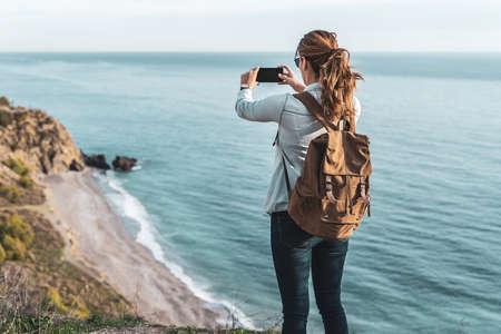 Jeune femme branchée avec un sac à dos explorant et photographiant la côte par une belle journée. Concept d'exploration et d'aventures