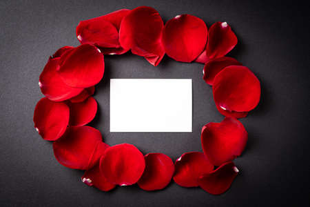 Red roses petals with a gift card to write on it on a black background. Concept of Valentine's Day, anniversary or mother's day.