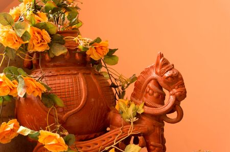 Clay horse with a chariot full of flowers set against an orange wall  Traditional Rajasthani art form used to depict the king
