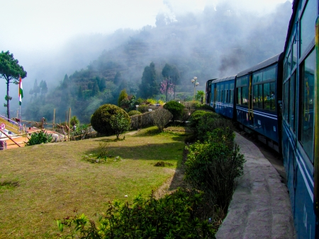 narrow gauge railways: Train passing a beautiful garden and entering into fog  Surrounded by tree covered mountains
