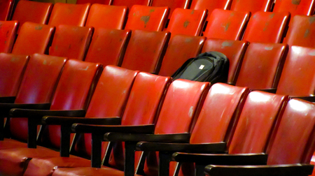 denote: Black bag lying on a seat in a row of empty seats in an auditorium  Can be used to denote loneliness or alone