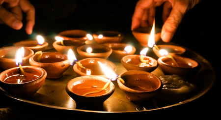 Hands lighting and picking up earthenware diwali lamps photo