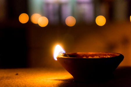denote: Earthenware diwali lamp set against the bokeh of diwali lights  Used to denote the victory of good over evil