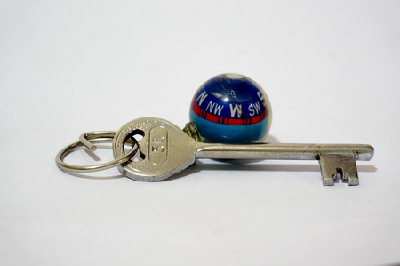 denote: Key with a globe shaped compass keychain  May be used to denote a key to travel, explore, adventure, relax and discover