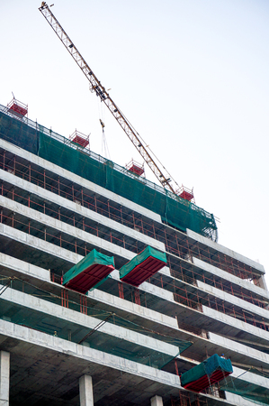 gurgaon: Construction work being done on a building using a crane and safety nets  The recent growth of India has been closely tied with numerous infrastructure projects