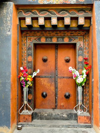 Beautifully painted and decorated wooden door flanked with flowers in Bhutan  This is the traditional architecture used in Bhutan and most buildings are required to confirm to it photo