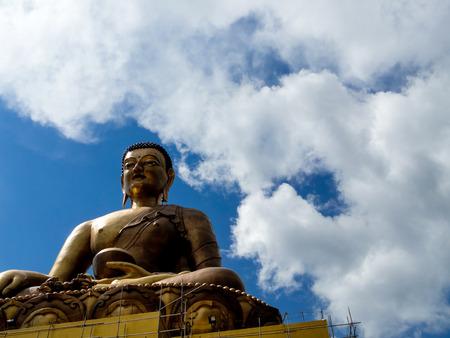 moksha: Golden statue of Buddha against a cloudy sky in bhutan  The statue shows him meditating