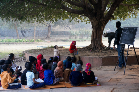 impart: Delhi, India  4th Jan 2014 - Poor children being taught in an open air classroom by volunteers  Classes like this  madrasa  are often held at the hauz khas village in Delhi India  This is to impart basic education to those who are unable to afford traditi