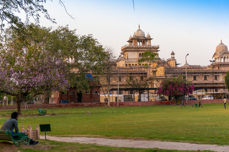 rajput: Jaipur, India - 22 March 2014: Man sitting on a park bench and looking at the Royal Albert hall museum in Jaipur