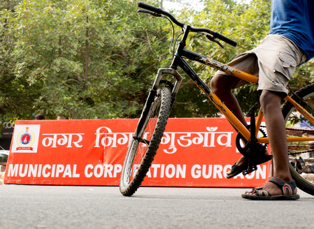 cordoned: Delhi, India; 10th Aug 2014 - Boy standing on a cycle near the Municipal corporation of Gurgaon board  The cordoned off streets on Rahagiri day give a chance to people to safely ride cycles or walk on the busy streets