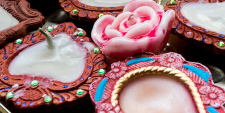 tradional: Tradional earthenware lamps (diya) hand made and decorated. Wax rose candle in the center Stock Photo