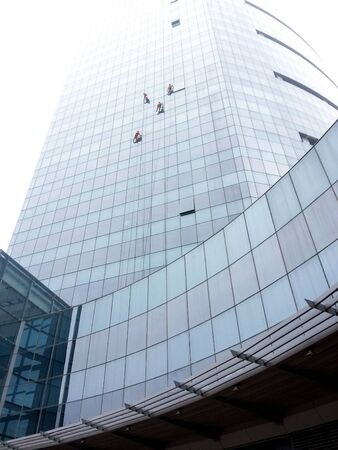 gurgaon: window cleaners climbing a glass building in gurgaon.
