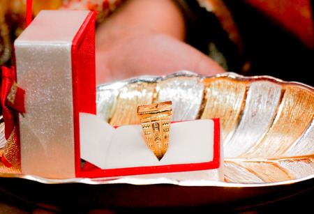 Golden wedding ring on a gold and silver tray. Presented to the bride or groom