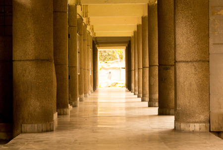 shiny floor: Empty hallway in a school during the summer break. Stone pillars and shiny stone floor are visible Stock Photo