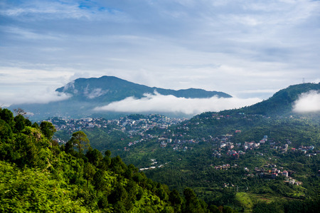 hill station tree: Clouds rolling between the hills of himachal pradesh in India. The small hill villages are visible among the green hills