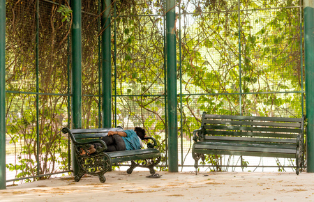 scorching: Gurgaon India 23rd May 2015: Man sleeping on a park bench in the shade of some plants. The summer heat has really hurt the homeless who have to find places to escape the scorching sun Editorial