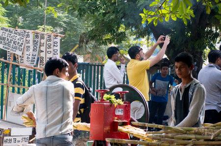 gurgaon: Delhi India 7th Jun 2015: Sugarcane juice vendor extracting fresh juice at a roadside stall