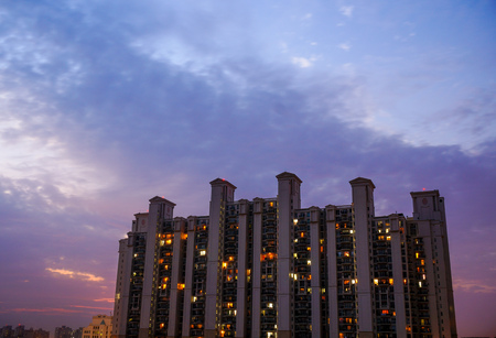 morning blue hour: Multistoried apartments in Gurgaon India against a colorful cloudy sky. The lights of the individual apartments are visible